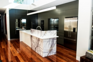 Beautiful intersecting Marble Island bench with contrast dark kitchen cupboards
