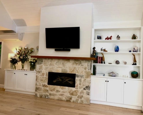 custom shelving and cupboards beside fireplace