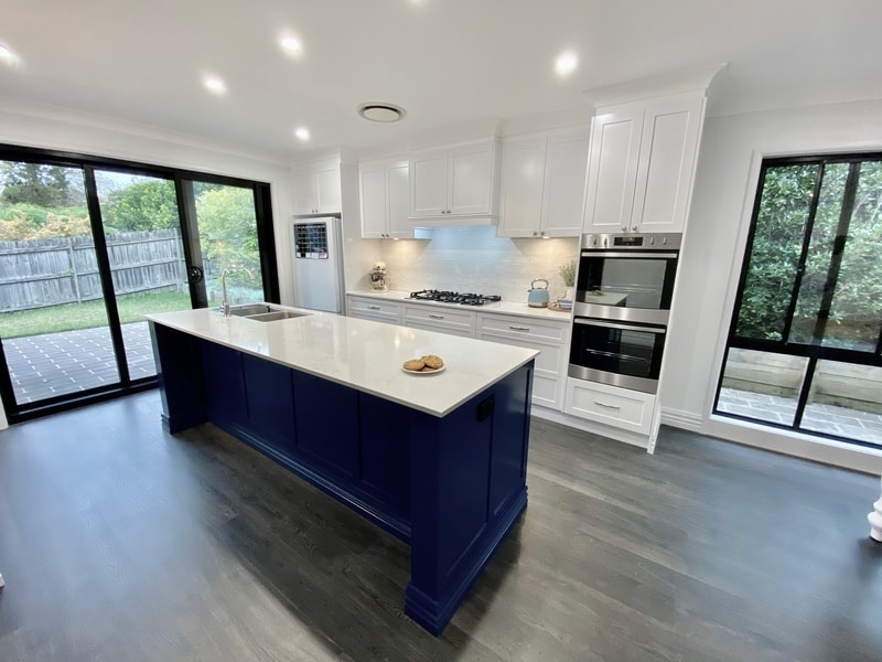 white custom kitchen with blue island cupboards
